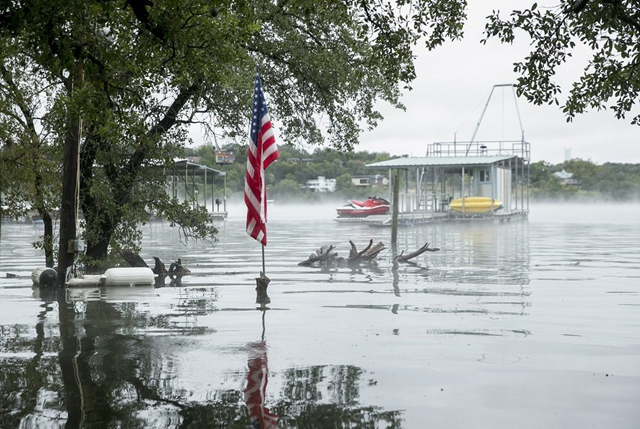 An American flag stands above the floodwaters in the backyard of a house at Graveyard Point on Lake Travis on Wednesday, 17 October 2018. Photo: Jay Janner / AP