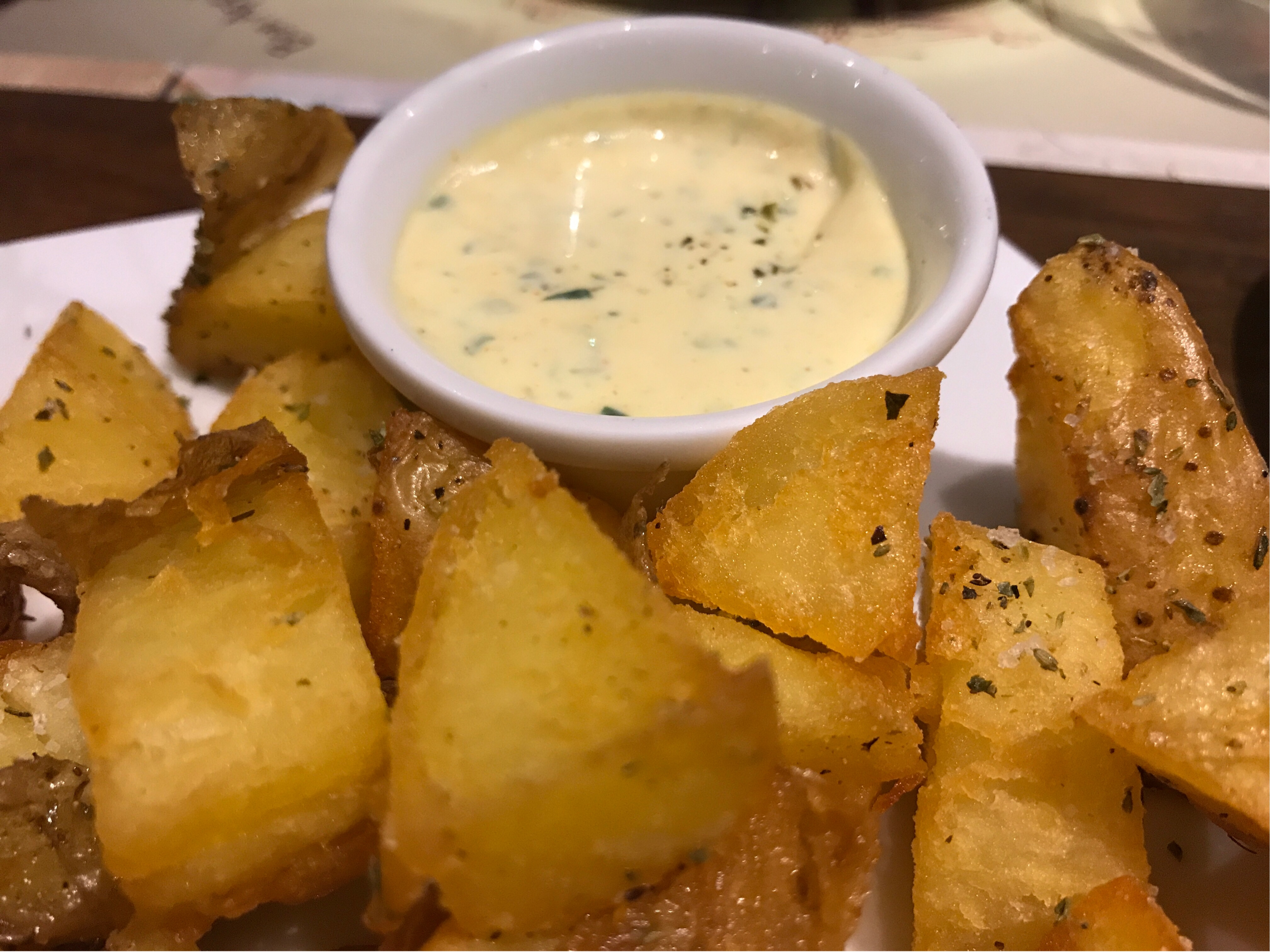 En skål med lysegul saus omgitt av potetbiter