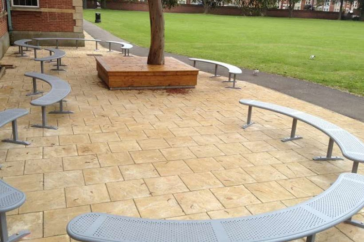 Curved perforated steel benches, painted silver, bolted down