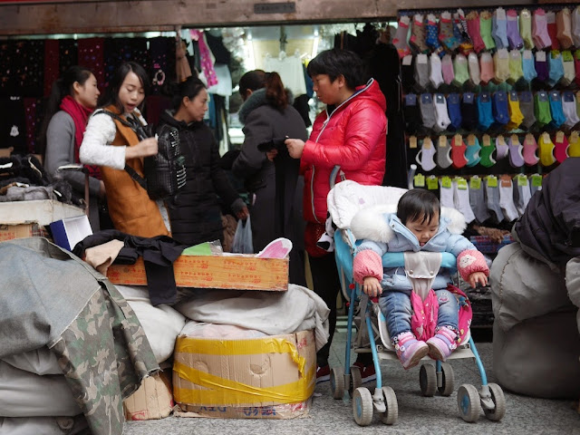 baby in stroller in front of a shop at the Xingwang International Finery City