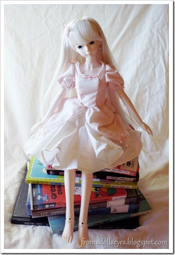 Ball Jointed Doll Sitting on a Stack of Library Books