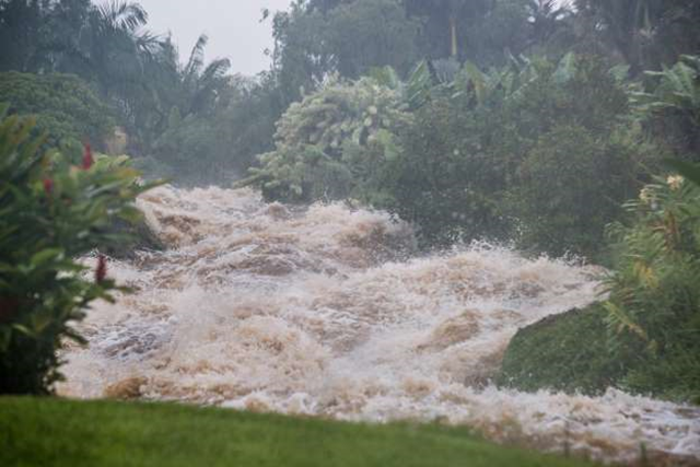 Heavy rainfall from Hurricane Lane causes a small stream to overflow onto Akolea Road in upper Kaumana, near Hilo, Hawaii, on 23 August 2018. Photo: Bruce Omori / EPA-EFE / REX / Shutterstock