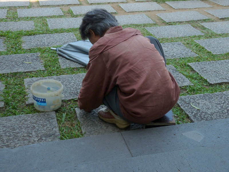 Dans un temple,arrachage manuel et delicat des mauvaises herbes