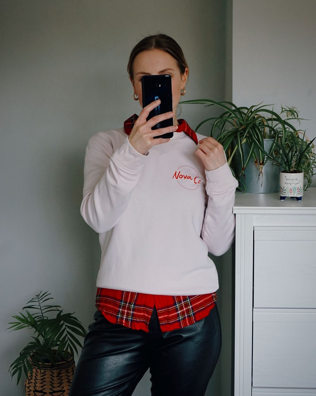 Amy is wearing a pink sweatshirt over a tartan shirt with black pleather trousers