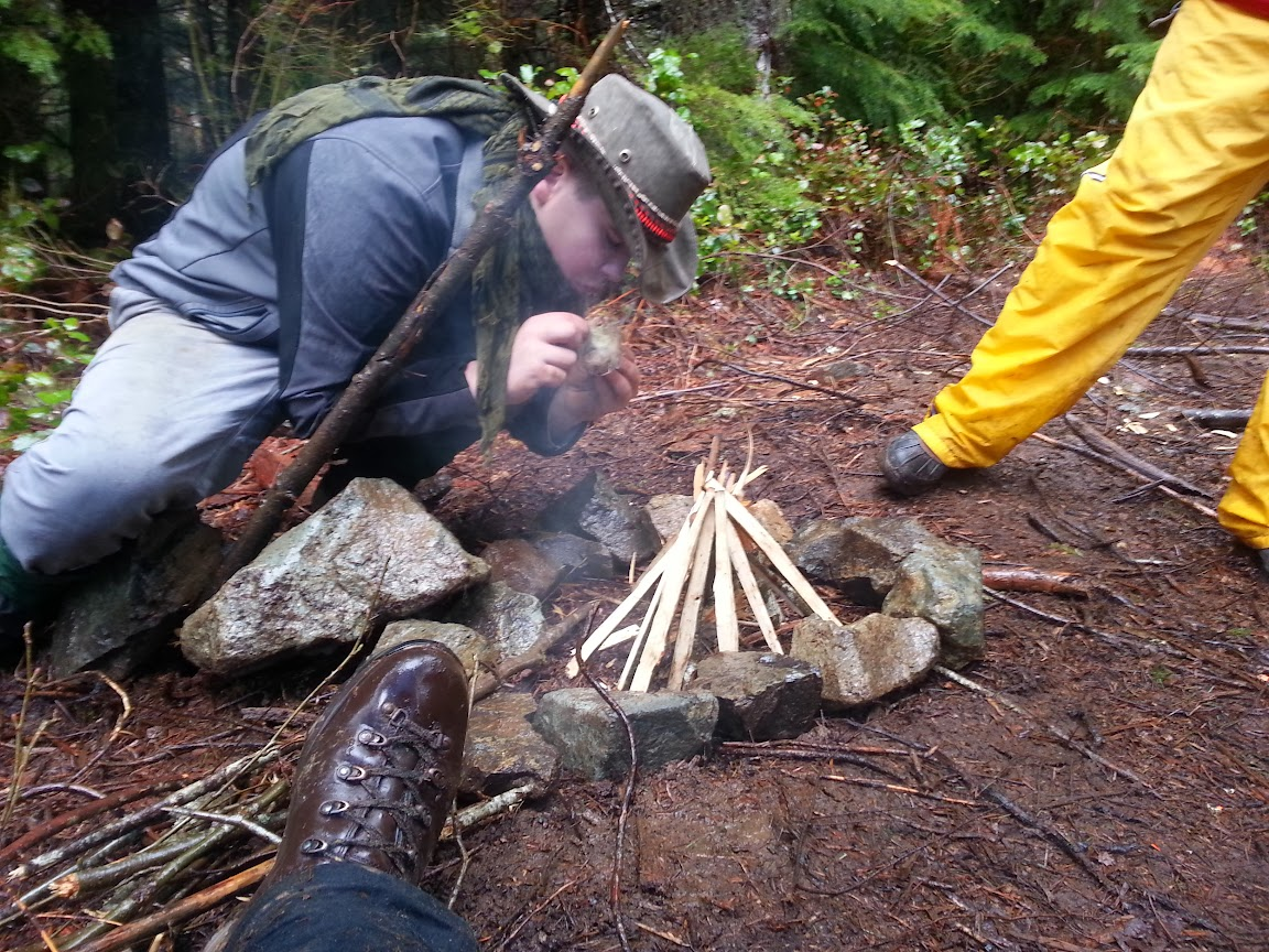 My son blowing charcloth embers to flame in the rain while wearing his RDB hat.