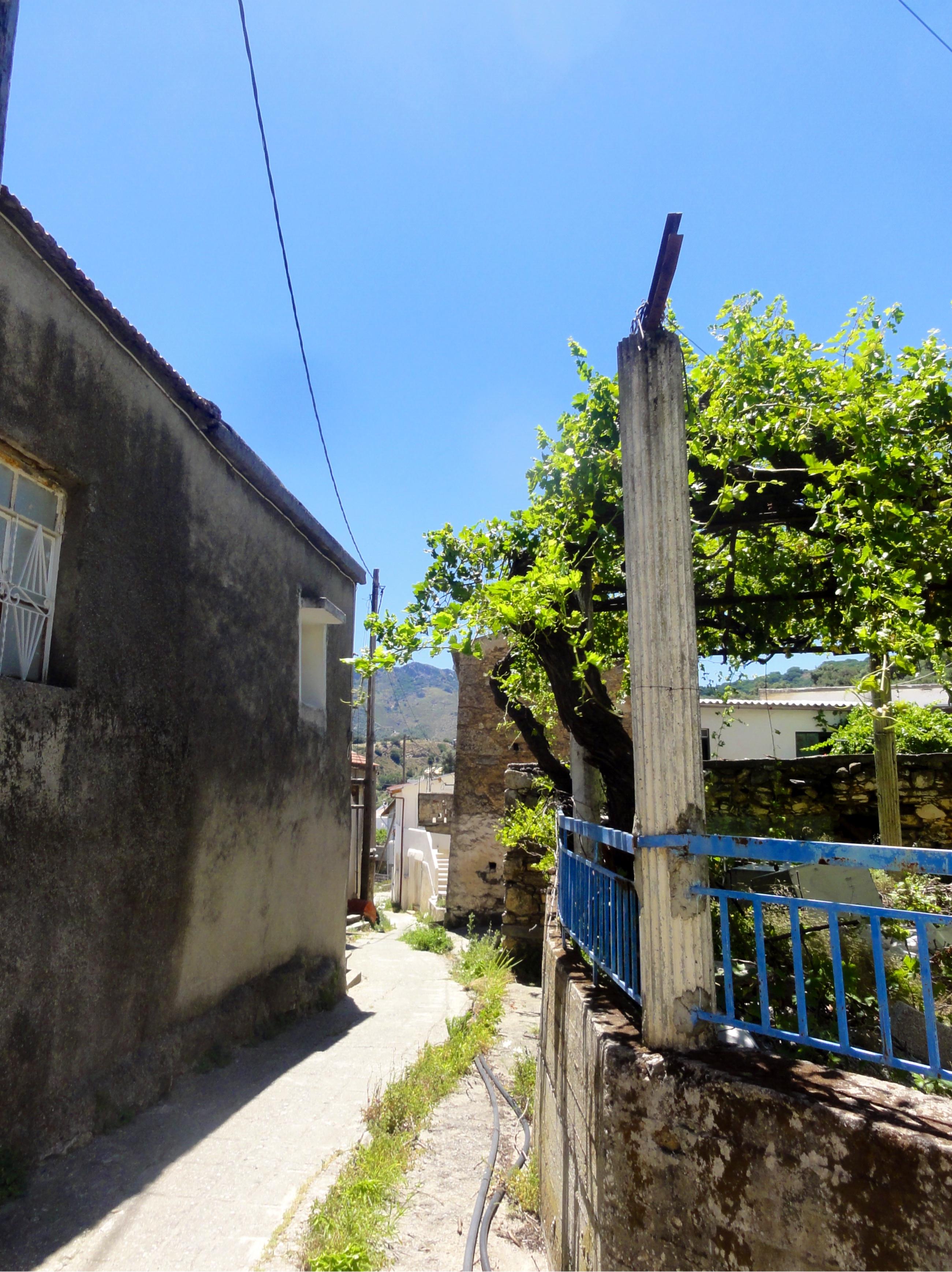 Trang grusvei med en murvegg på den ene siden og en frodig terrasse på den andre.