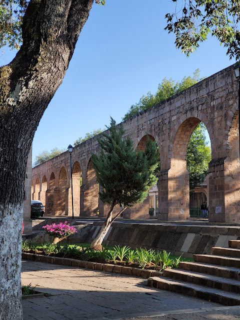 View of Morelia aqueduct from a public park. Trees, green plants, flowering plants, stone steps help make up the composition.