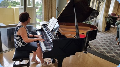 Club Treasurer, Mary Elvin, playing the Village's Kawai grand piano.