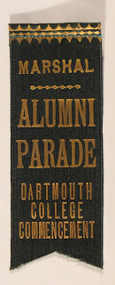 "A dark green ribbon with gold text reading ""Marshal Alumni Parade Dartmouth College Commencement."""
