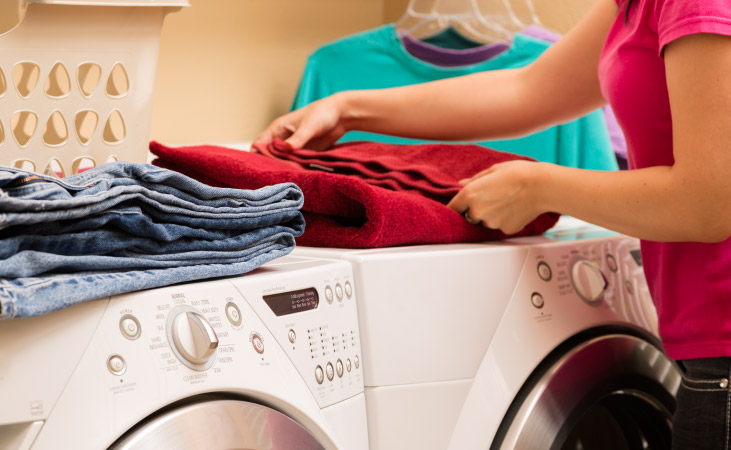 A woman folding her laundry on top of her dryer