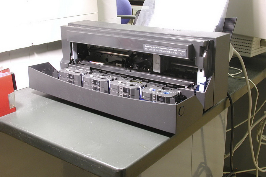 Met een OKI printer kun je alle kleuren drukken op transparant decal. Deze matrixprinter (van PB messing Modelbouw) maakt gebruik van inkt op verschillende naast elkaar geplaatste linten. Dit is goed te zien op de foto. Behalve zwart, cyaan, magenta en geel kun je met de OKI PD-5000 printen in goud, zilver, wit en metallic kleuren.