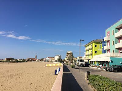 En strandpromenade med strand til venstre og en rekke med hotelle til høyre.
