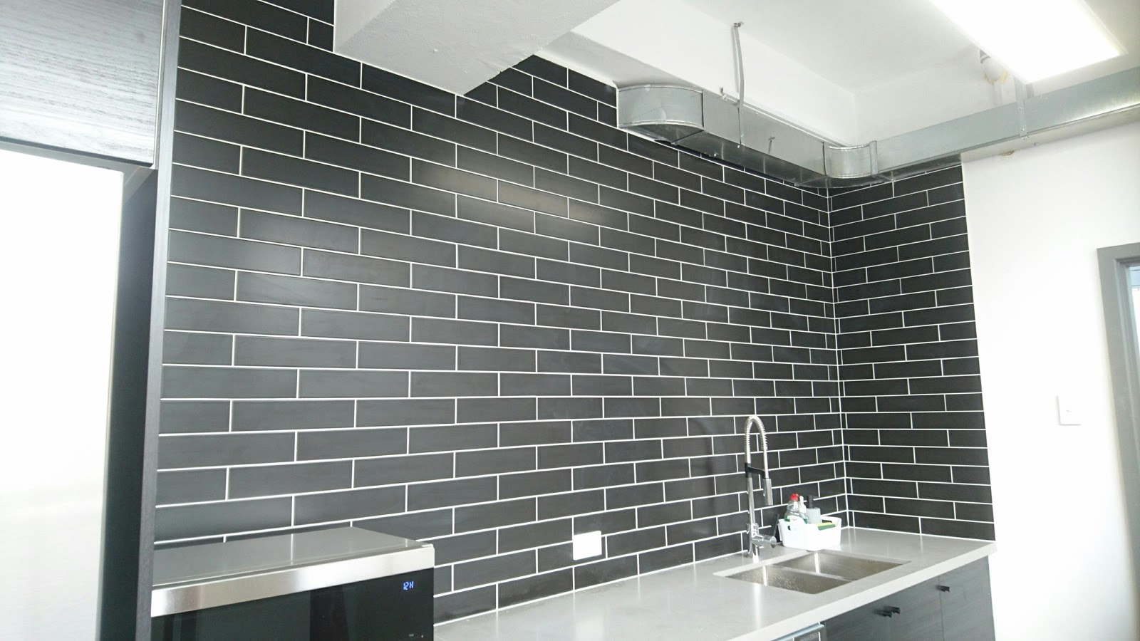 Black glossy subway tiles with white grout definitely a feature of this business now