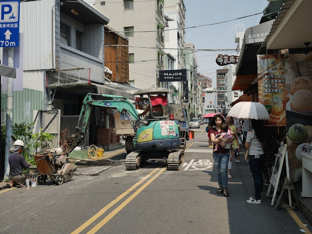 woman carrying a baby past construction work by the Taiwan Water Corporation at Zhengxing Street in Tainan