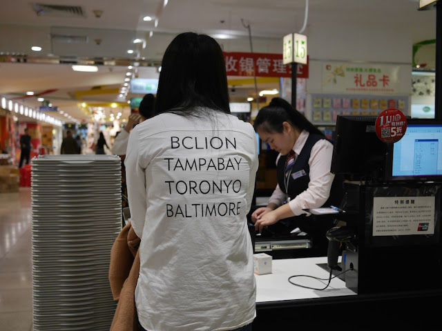 "shirt with words ""BCLION"", ""TAMPABAY"", ""TORONYO"", and ""BALTIMORE"""