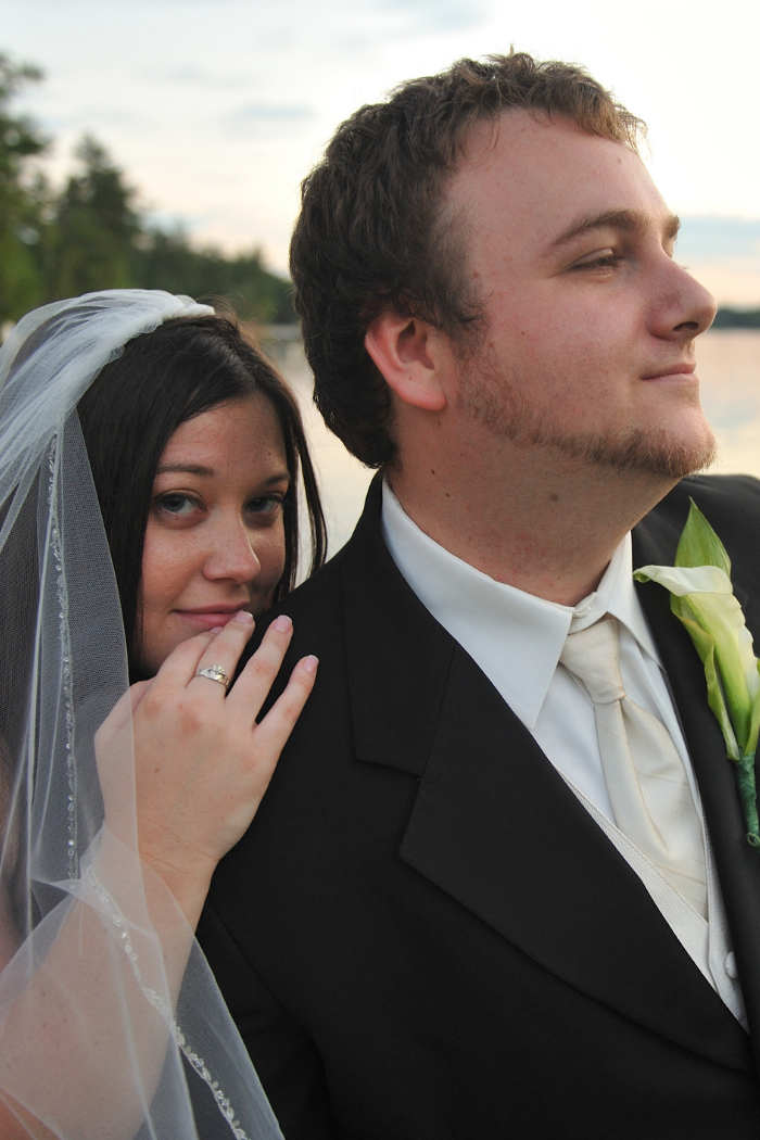 bride looking at the camera with her hand on her husbands shoulder