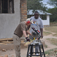 Peter cutting wood on the mitre saw with Machaa looking on.