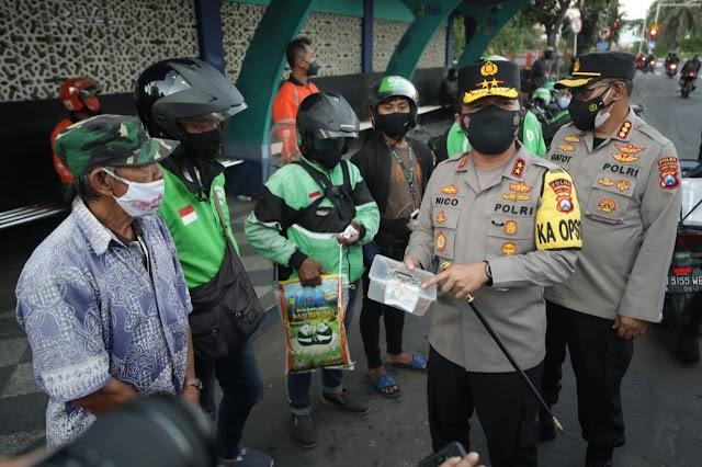 Kapolda Jatim Bagikan Beras dan Kenakan Masker Pada Anak Kecil yang Tak Kenakan Masker