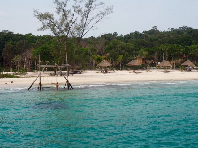 Sun beds on the beach and ocean swing, taken from the pier at Nature Beach, Koh Rong, Cambodia