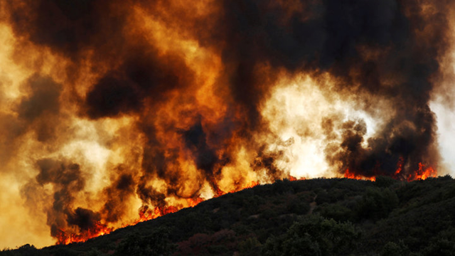Flames roll over a hill toward homes near Lakeport, California, on 2 August 2018. The effects of rapid climate change are being felt across the world. Photo: Fred Greaves / Reuters