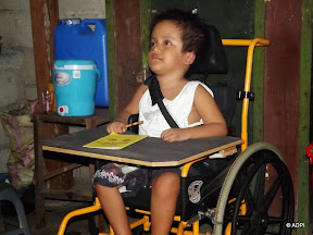 A young boy in a new wheelchair, with pen and paper