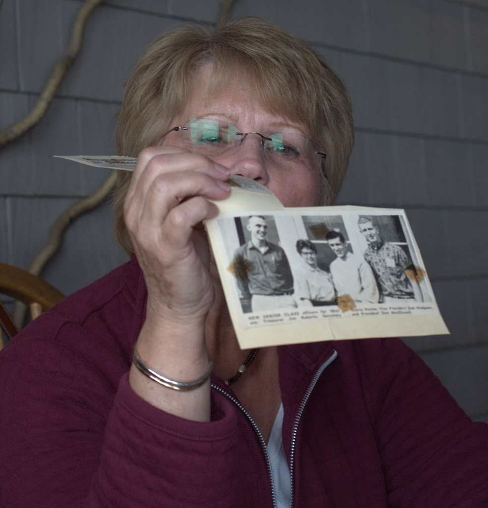 Gloria Hanke looking at a photo of senior class officers:  Jim Roberts, Gloria Hanke, Bob Hodgson, Don McDowell