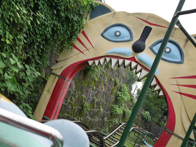 about to go through a giant cat's mouth while riding a roller coaster