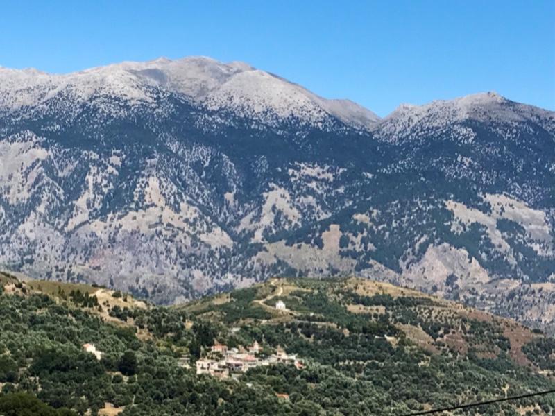 Karrig fjellside i bakgrunnen. I forgrunnen en mer frodig høyde med liten landsby.