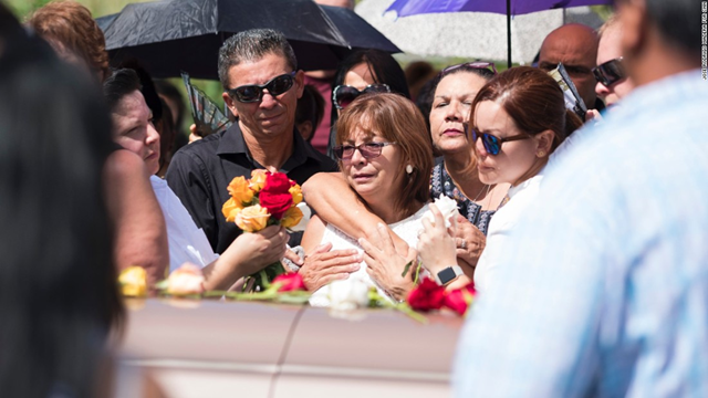 At the funeral of Isabel Rivera, Evelyn Cruz Rivera, one of Isabel Rivera's five children, stands at her mother's coffin. On 15 October 2017, three weeks after Hurricane MAria hit Puerto Rico, Isabel Rivera died awaiting a procedure at a hospital that had lost power in the hurricane and whose backup generator failed. Photo: CNN
