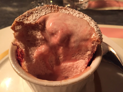 Strawberry coulis and pouring cream flowing through the soufflé