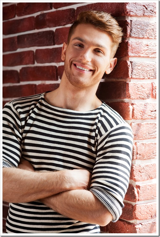 Handsome in striped shirt. Cheerful young man in striped shirt looking at camera and smiling while leaning at the brick wall