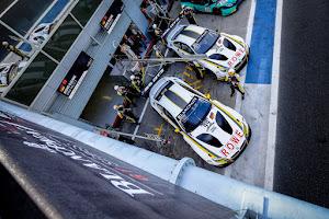 racewagens in de pits van bovenaf genomen
