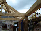 King post trusses and purlins in Green Oak with Roman numerals marking the joints