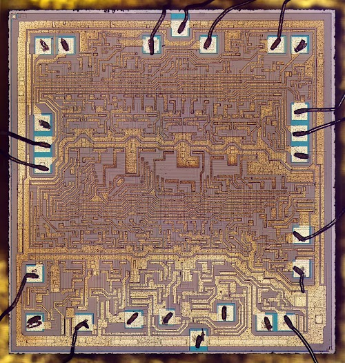 Die photo of the 74181 ALU chip. The metal layer of the die is visible; the silicon (forming transistors and resistors) is hidden behind it.