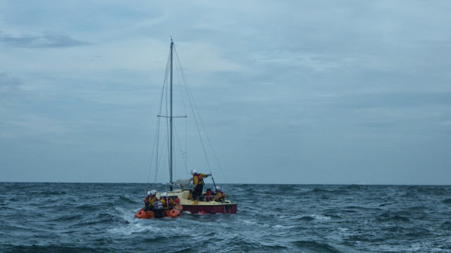 Swanage D-class lifeboat takes two of Poole's crew members across so they can board the 23ft yacht south of Old Harry Rocks - 28 September 2013. Photo credit: RNLI / Rob Inett