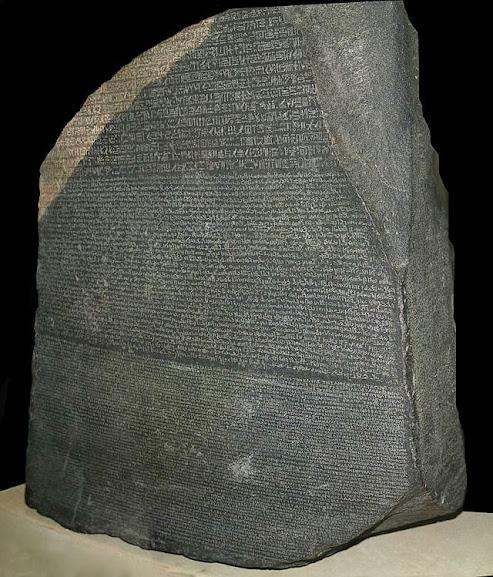 A estela de Roseta trazia três textos iguais escritos em línguas diferentes. Na porção de cima trazia hieróglifos egípcios, na porção do meio, trazia o texto em demótico e na debaixo, em grego.