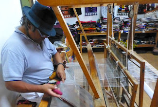 Photo: Textile artist in another workshop nearby works at foot-powered loom