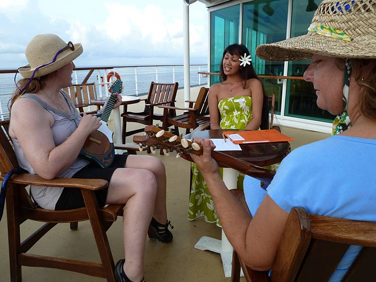 Two passengers take ukelele lessons from a member of Les Gauguines aboard ms Paul Gauguin.