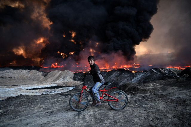 A boy pauses on his bike as he passes an oil field that was set on fire by retreating ISIS fighters ahead of the Mosul offensive, on 21 October 2016 in Qayyarah, Iraq. Photo: Carl Court / Getty Images