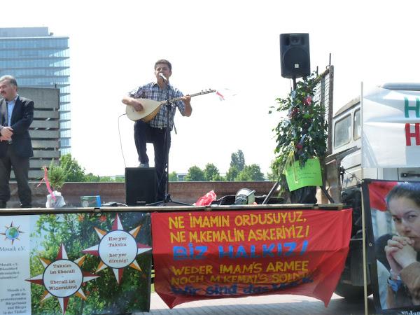 Liedermacher auf der mit Trarnsparenten geschmückten Bühne.