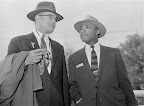 """King's Montgomery Bus Boycott - Trial Rev. Martin Luther King, Jr., speaks with C. Ewbank Tucker, one of his eight attorneys and also a preacher, as both arrived at the Montgomery County courthouse March 22, 1956, for the fourth day of King's trial in the city's bus boycott. From the original caption: """"Defense attorneys said they might put King on the stand. Ninety blacks are charged with violation of the state boycott law."""" (AP/Wide World Photos)"""