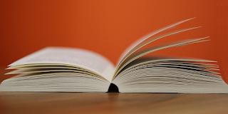 An open book on a wooden desk