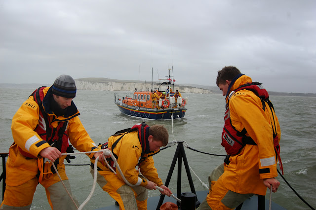 Poole lifeboat Crew Member Ed Davies overseeing two trainees - Joe Manning and Anthony Skerman - attaching the tow rope to the staghorn bollard during a training exercise with Swanage all-weather lifeboat in Poole Bay on Sunday 23 February 2014. Photo: RNLI/Dave Riley