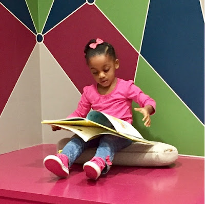 Childhood development milestones stay at home mom black brown girl reading northwest library at scotts crossing atlanta georgia toddler