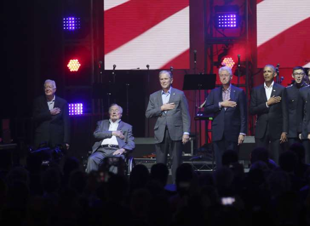 Former Presidents from right, Barack Obama, Bill Clinton, George W. Bush, George H.W. Bush and Jimmy Carter place their hands on their chest for the national anthem on stage at the opening of a hurricanes relief concert in College Station, Texas, Saturday, 21 October 2017. All five living former U.S. presidents joined to support a Texas concert raising money for relief efforts from Hurricane Harvey, Irma and Maria's devastation in Texas, Florida, Puerto Rico and the U.S. Virgin Islands. Photo: LM Otero / AP Photo
