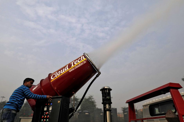 A man operates an 'anti-smog gun' in Delhi, a machine that sprays atomised water into the air, 23 February 2018. Photo: Saumya Khandelwal / Reuters