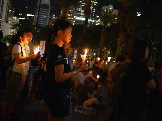 young woman holding a candle at the vigil in Victoria Park, Hong Kong, commemorating the anniversary of the Tiananmen Square crackdown