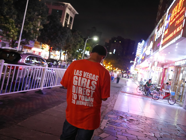 "Man wearing shirt with words ""Las Vegas Girls Direct To You In 20 Minutes"" on back"
