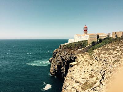 Et fyrtårn på en høy klippe over et opprørt hav-