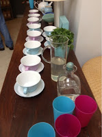 teacups and saucers, water jugs and plastic drinking cups